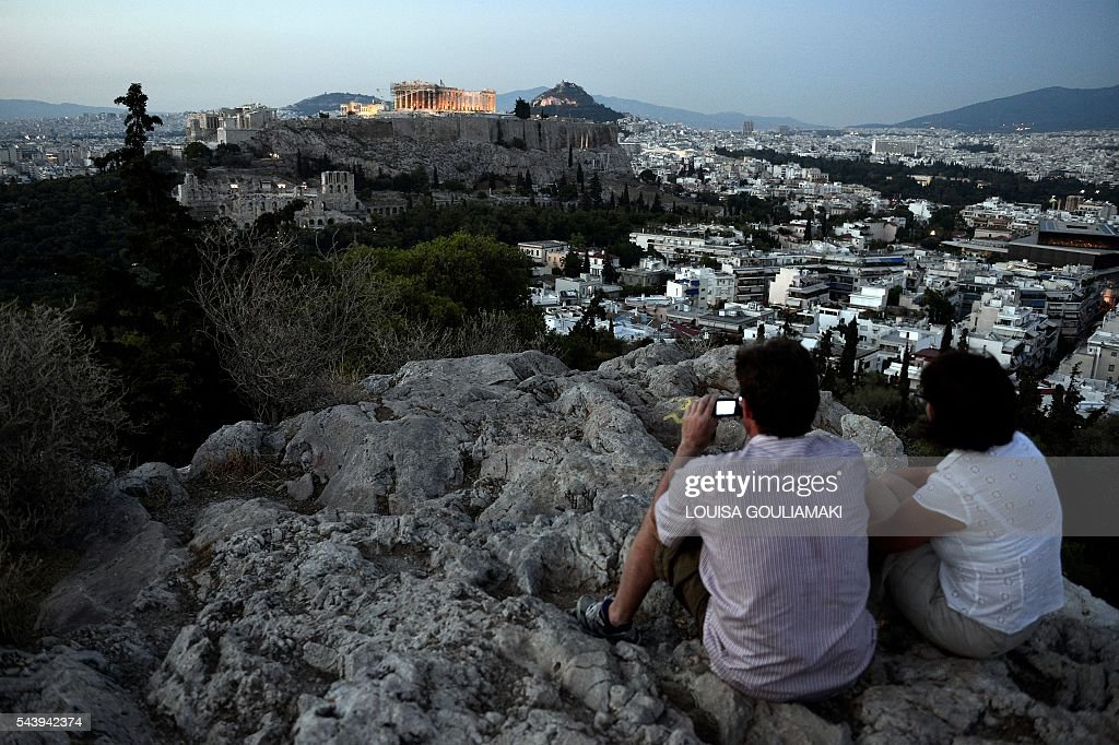 Tourist enjoy an evening sightseing view of the Acropolis in Athens on June 30, 2016. / AFP / LOUISA