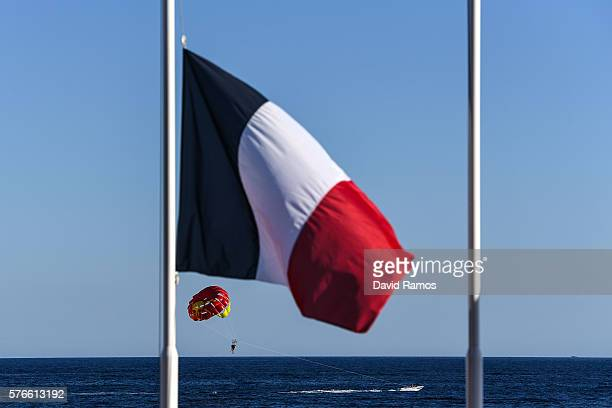 Tourist enjoy parasailing as a French flag flies at half mast on the Promenade des Anglais on July 16 2016 in Nice France Five people believed to be...
