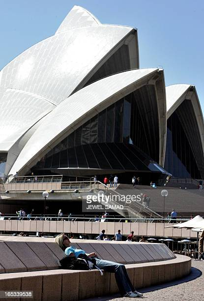 A tourist enjoys the sun near the Sydney Opera House as the city prepares for the AsiaPacific Economy Cooperation summit 02 September 2007 A massive...