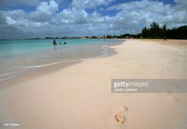 Tourist families enjoy at a beach in Bridgetown on April 12 2012 Historically the economy of Barbados had been dependent on sugarcane cultivation and...