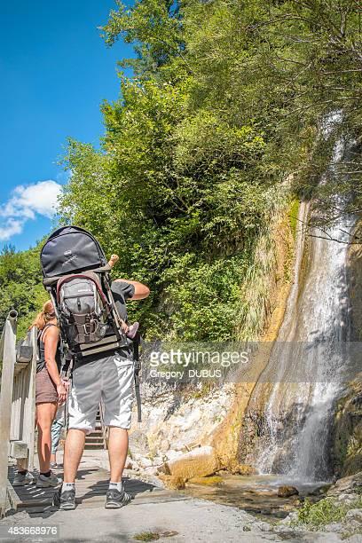 Vacances en famille à la recherche à une cascade au cours de la randonnée en été