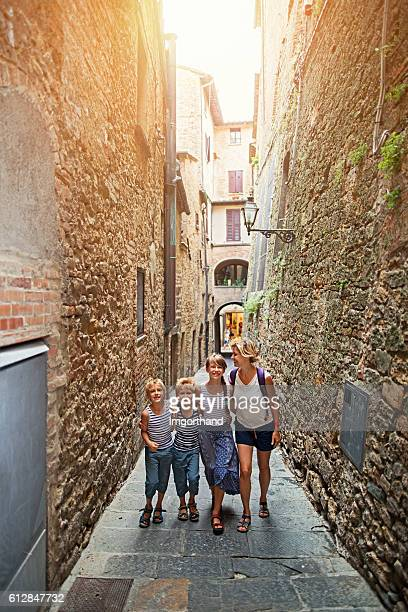 Tourist family walking narrow street in Italian town Volterra Tuscany