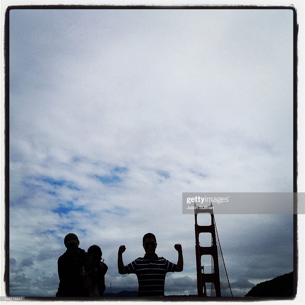 A tourist flexes his muscles while having his picture taken near the Golden Gate Bridge on May 3, 2012 in Sausalito, California. The Golden Gate Bridge, Highway and Transportation District is preparing for the 75th anniversary of the iconic Golden Gate Bridge that will be marked with a festival on May 26 - 27 that will feature music, displays of bridge artifacts and art exhibits. The 1.7 mile steel suspension bridge, one of the modern Wonders of the World, opened to traffic on May 27, 1937.