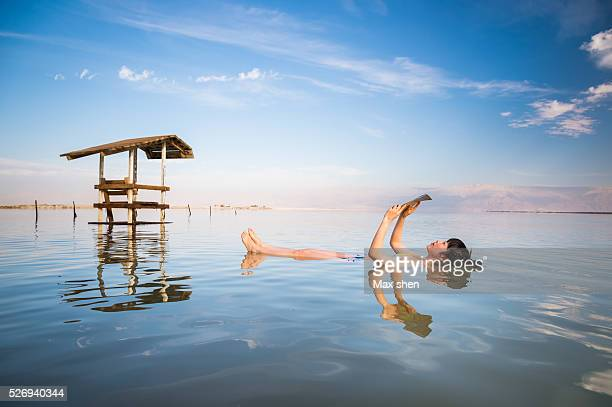 Tourist floating reading in Dead Sea in Israel