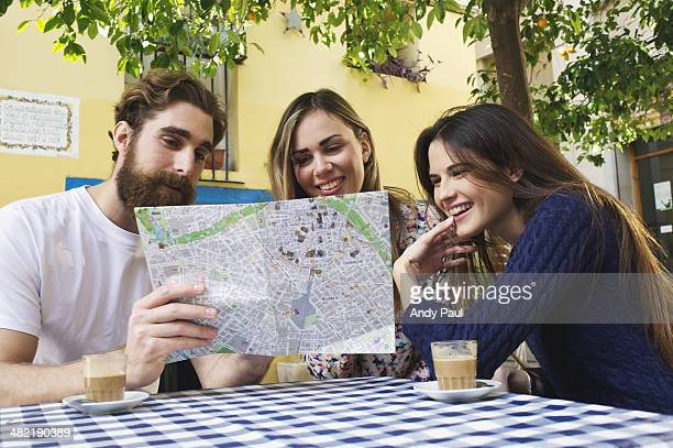 Tourist friends looking at map at sidewalk cafe, Valencia, Spain
