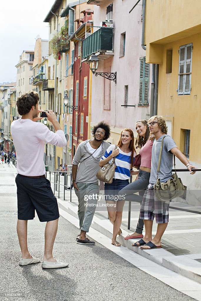 Tourist friends taking pictures of each other. : Stock Photo