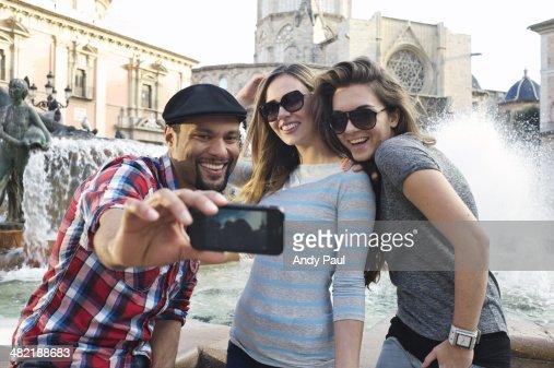 Tourist friends taking self portrait, Plaza de la Virgen, Valencia, Spain
