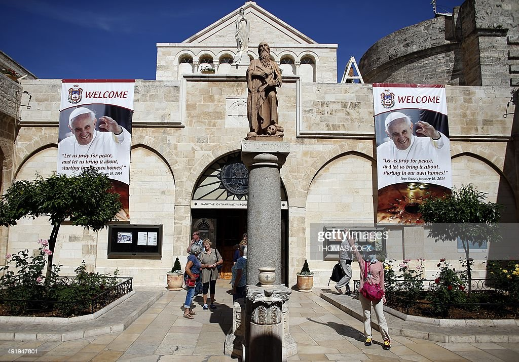 A tourist from Asia has her photograph taken in front of a banner bearing the portrait of Pope Francis on May 18, 2014, inside the yard of Saint Catherine's Church in the Church of Nativity, in the West Bank Town of Bethlehem. The pope's visit is scheduled to begin in Jordan on May 24, and he is then due to spend two days in the Holy Land from May 25.