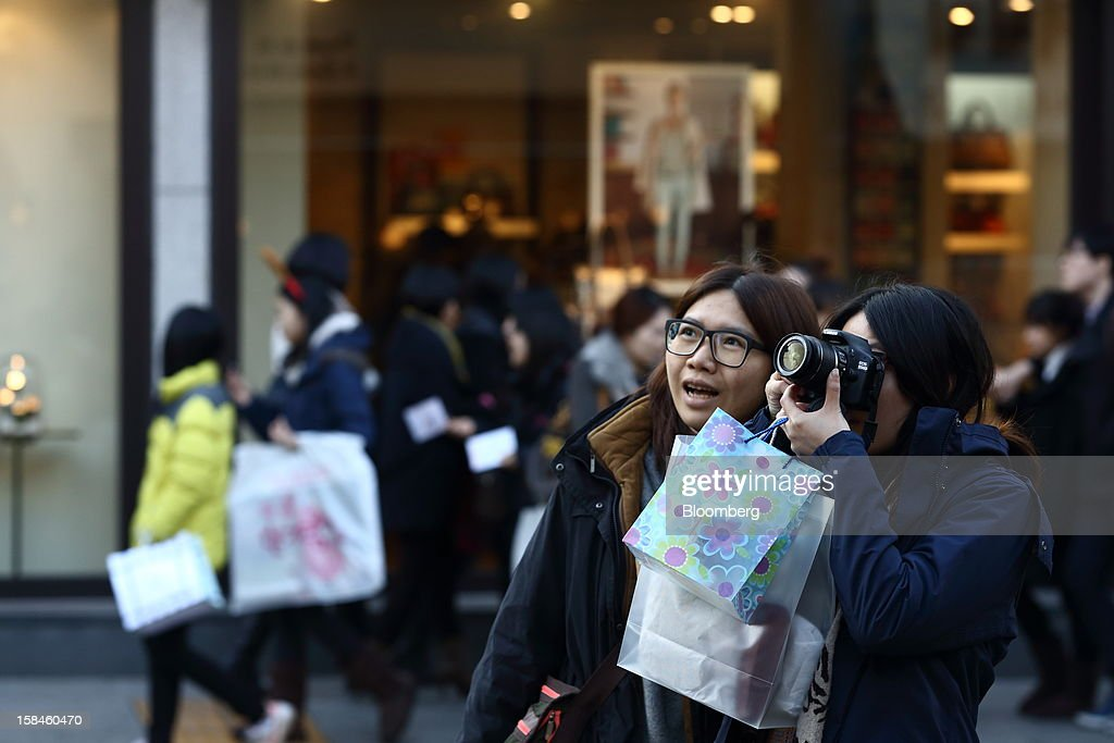 A tourist from Taiwan takes photographs on Garosugil street in the Gangnam district of Seoul, South Korea, on Saturday, Dec. 15, 2012. South Koreans vote on Dec. 19 to replace President Lee Myung Bak, whose five-year term ends in February. Photographer: SeongJoon Cho/Bloomberg via Getty Images
