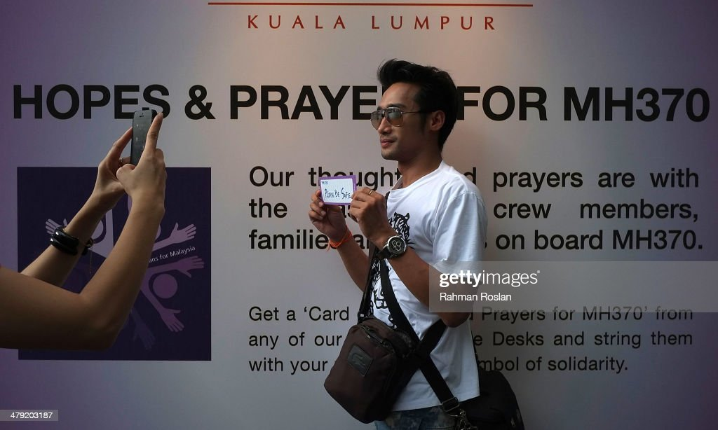 A tourist from Thailand poses with his well wish card dedicated to the flight MH370, March 17, 2014 in Kuala Lumpur, Malaysia. The search area for Malaysia Airlines flight MH370 has increased again to include both land and water from Kazakhstan to the southern Indian Ocean following reports the airliner flew for several hours after last contact. The missing aircraft disappeared one week ago carrying 227 passengers and 12 crew on route from Kuala Lumpur to Beijing. All passengers and crew are currently under investigation and 22 countries are involved in the search.