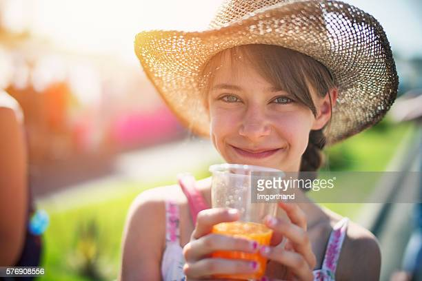 Tourist girl drinking a glass of freshly squeezed orange juice