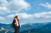 Long hair brunette girl on the top of the mountain enjoying fresh air