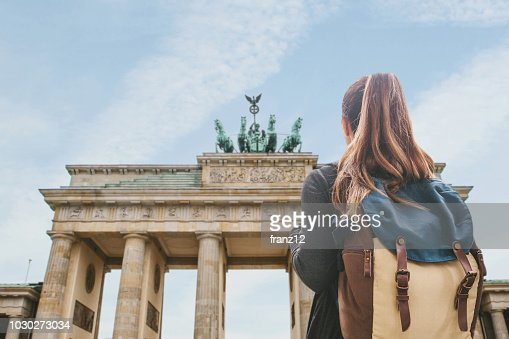 A tourist girl with a backpack looking at the Brandenburg Gate in Berlin : Stock Photo