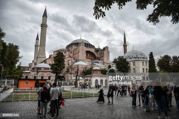 A tourist guide give informations in front of the Hagia Sophia on August 22 2017 during a rainy day in Istanbul / AFP PHOTO / OZAN KOSE