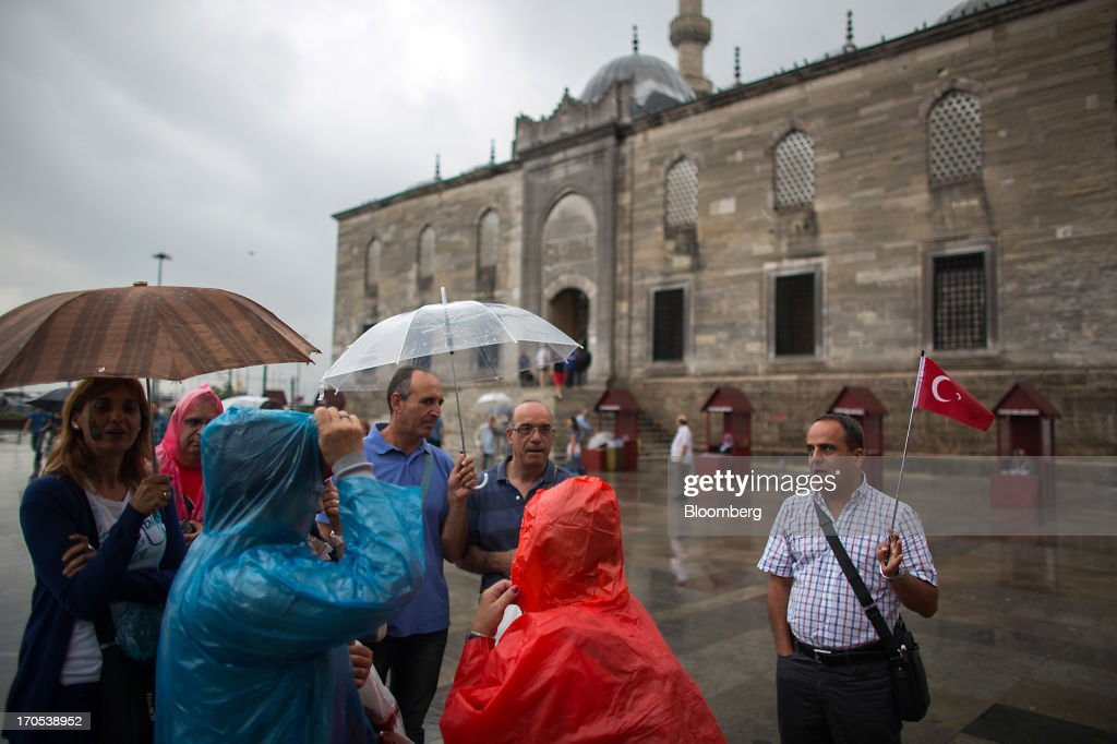 A tourist guide holds a Turkish national flag as he speaks to his tour group outside the Tahtakale shopping district in Istanbul, Turkey, on Friday, June 14, 2013. The law forbids the sale of alcohol at night and near schools and mosques, going against the secular traditions of the Muslim-majority country of 74 million, where many people drink and women often choose not to cover their hair. Photographer: Lam Yik Fei/Bloomberg via Getty Images