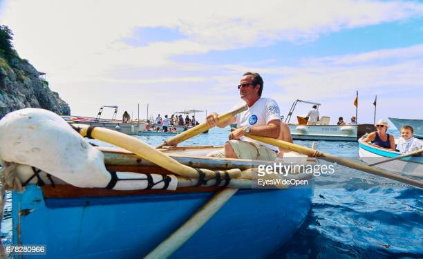 Tourist Guide in a small rowing Boat for the Blue Grotto at the Island of Capri on June 24 2015 in Naples Italy