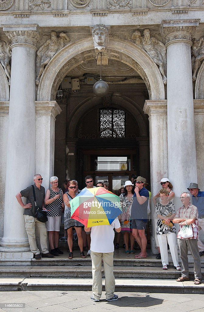 A tourist guide stands under an umbrella while conducting a tour through the city in St Mark's Square on June 21, 2012 in Venice, Italy. An intense heatwave is sweeping across many regions in Italy, prompting the country's health ministry to issue a number of high level alerts.