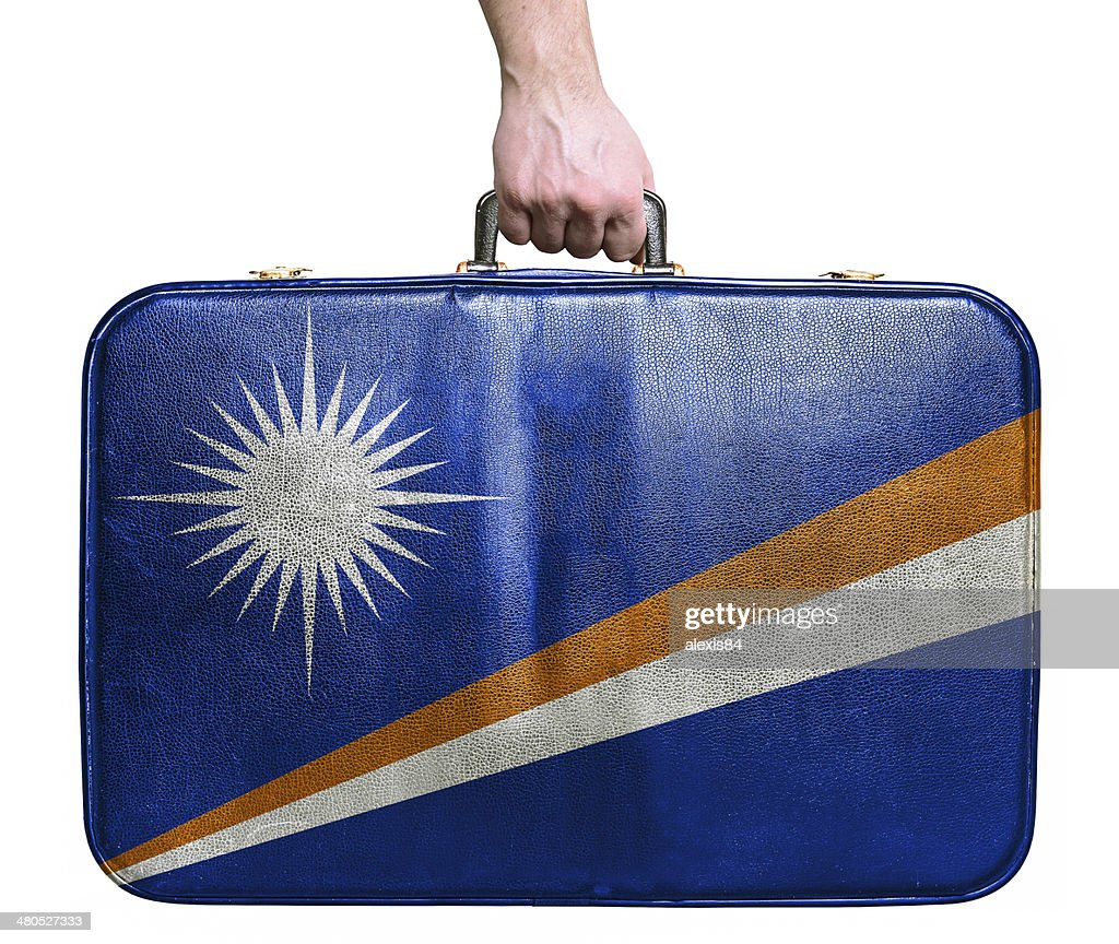 Tourist hand holding vintage travel bag flag of Marshall Islands : Stock Photo