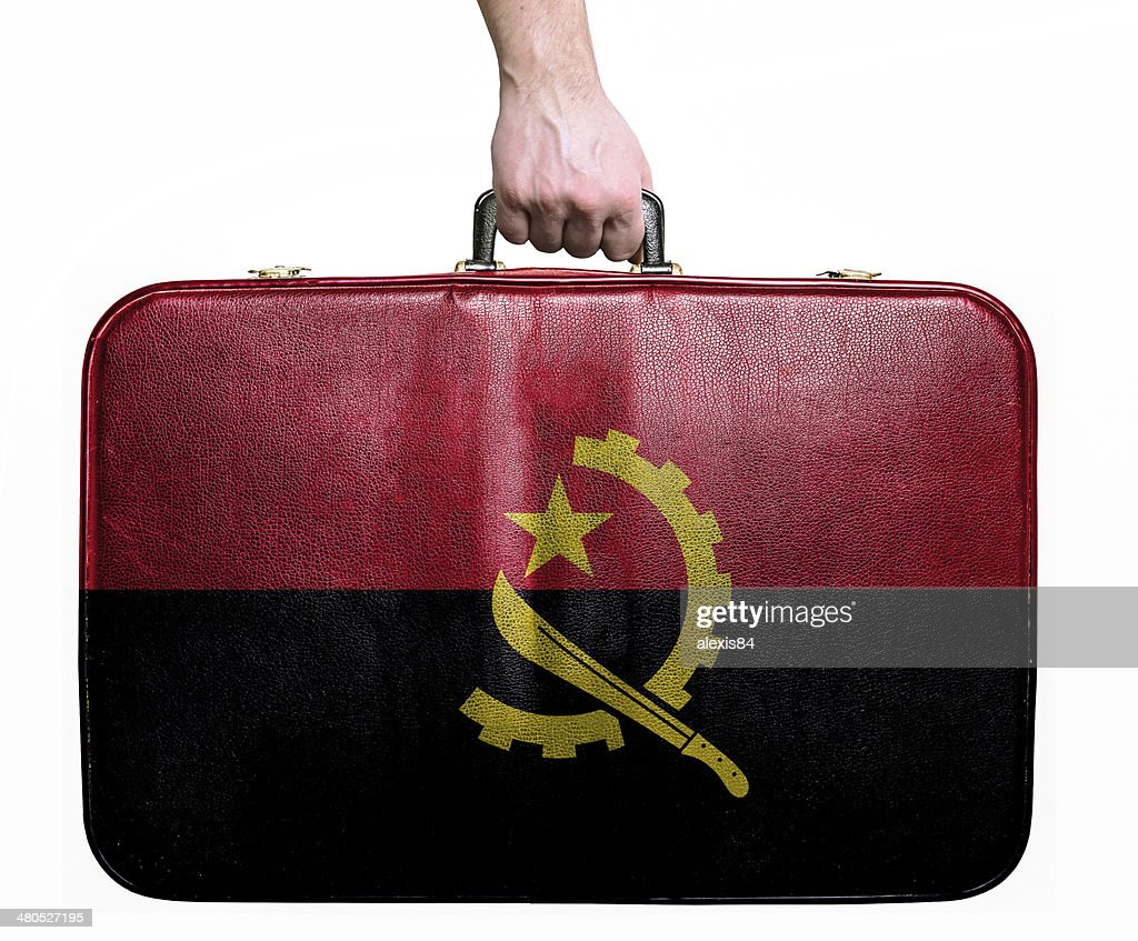 Tourist hand holding vintage travel bag with flag of Angola : Stock Photo