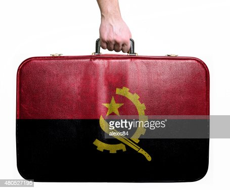 Tourist hand holding vintage travel bag with flag of Angola : Bildbanksbilder