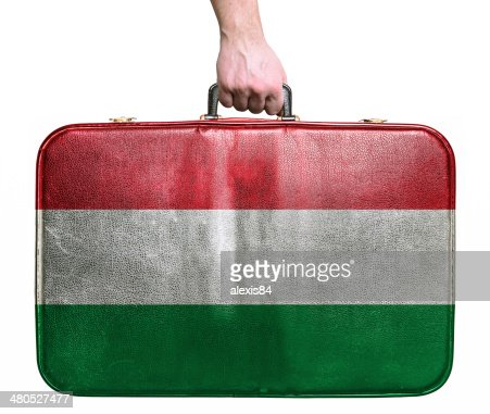 Tourist hand holding vintage travel bag with flag of Hungary : Stock Photo