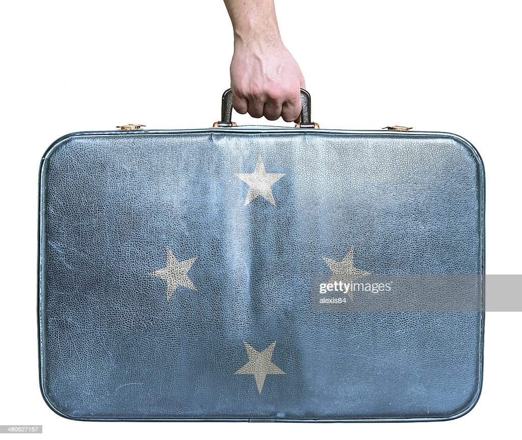 Tourist hand holding vintage travel bag with flag of Micronesia : Stock Photo