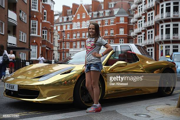 A tourist has her photograph taken next to a Gold Ferrari in Knightsbridge on August 8 2014 in London England Tourists and car enthusiasts have been...