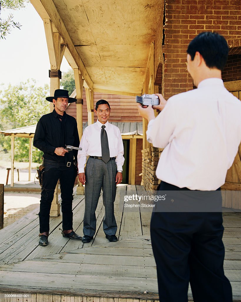 Tourist having picture taken with old west gunslinger : Stock Photo