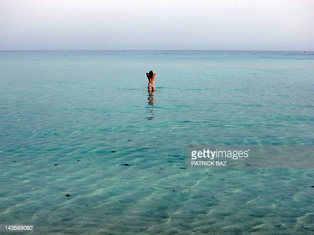 A tourist heads for a swim on Nissi Beach in the Cypriot resort town of Ayia Napa on April 29 2012 AFP PHOTO/PATRICK BAZ