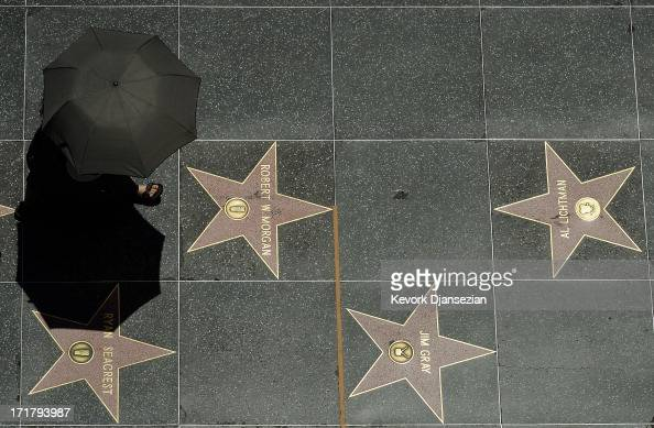 A tourist holding an umbrella to shield herself from the sun walks on Hollywood Walk of Fame stars during a major heat wave in Southern California on...