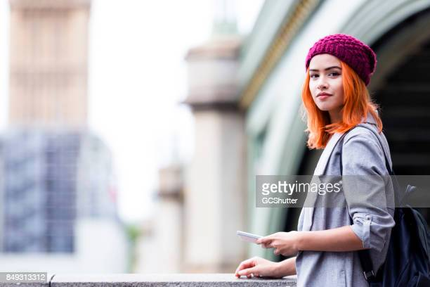 Tourist holding her smart phone with looking at the camera