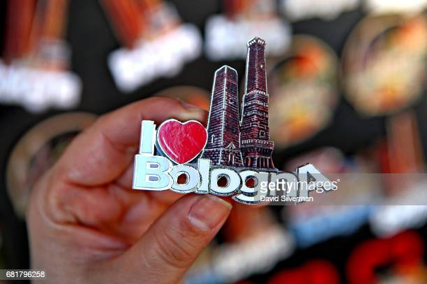 A tourist holds a fridge magnet showing the city's iconic Two Towers Le Due Torri of Garisenda and Asinelli on March 31 2017 in Bologna Italy As many...