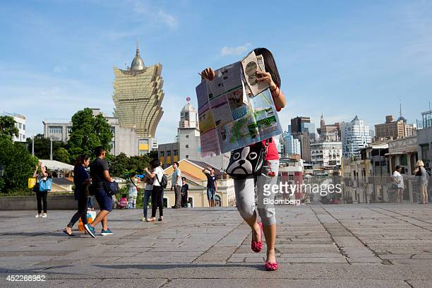 A tourist holds a map as Casino Grand Lisboa operated by SJM Holdings Ltd center left stands in the background in Macau China on Wednesday July 16...
