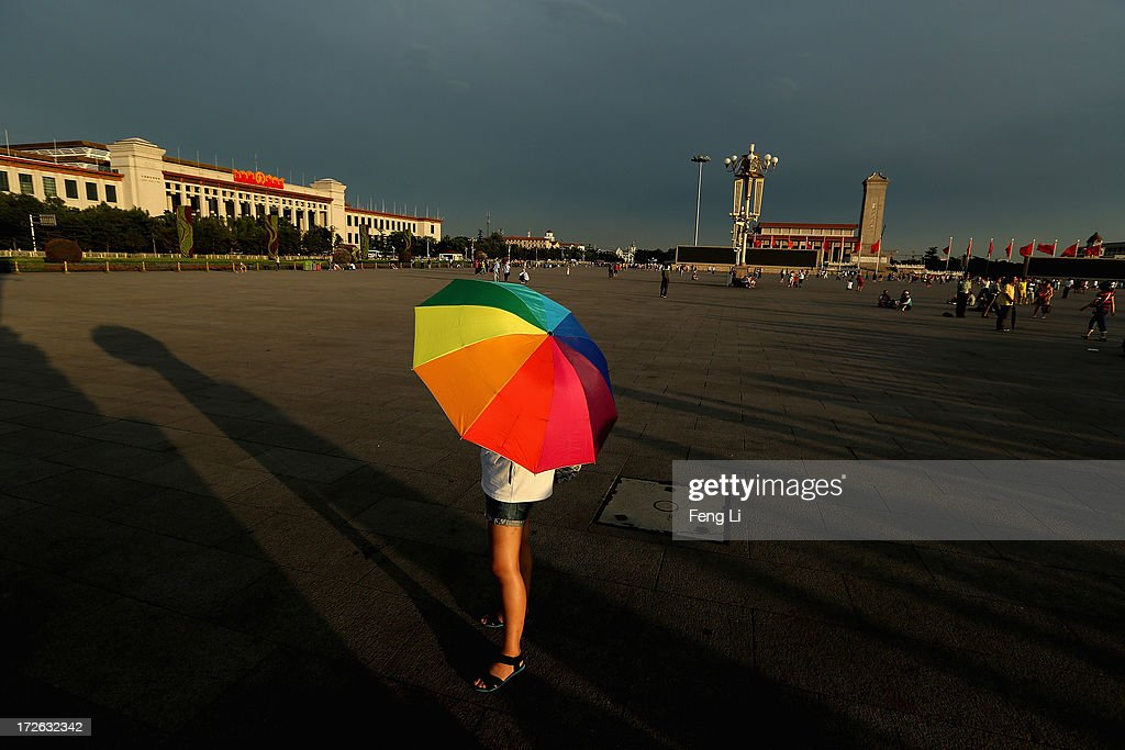 A tourist holds the parasol waiting for the customary ceremony of lowering flag at Tiananmen Square after several days of heavy air pollution on July 4, 2013 in Beijing, China.