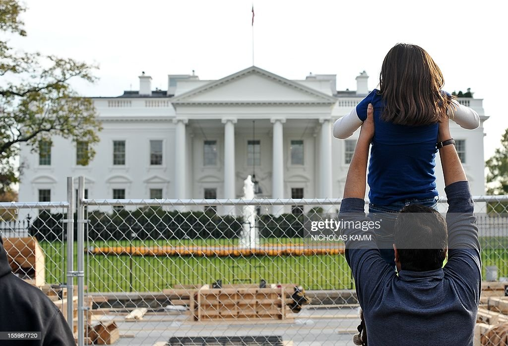 A tourist holds up his daughter to look at the White House as construction for US President Barack Obama's second inauguration is under way in Washington on November 10, 2012. Obama won Florida's 29 electoral votes in the presidential election on November 10, further fattening his substantial margin of victory in what had been predicted to be a close race. The state was the last to report its tally from the election November 6, in which Obama beat Republican Mitt Romney. With Florida's votes in the electoral college, the president's total goes up to 332, against 206 for Romney. AFP PHOTO/Nicholas KAMM