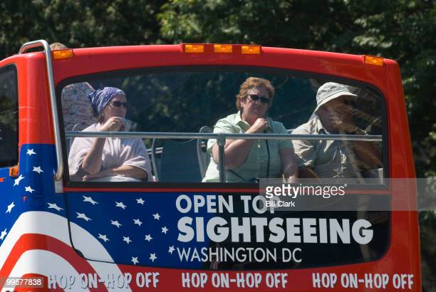 A tourist in a double decker tour bus tries to cool down by fanning herself as the bus sits at a stop light at New Jersey Ave and D St NW on Monday...