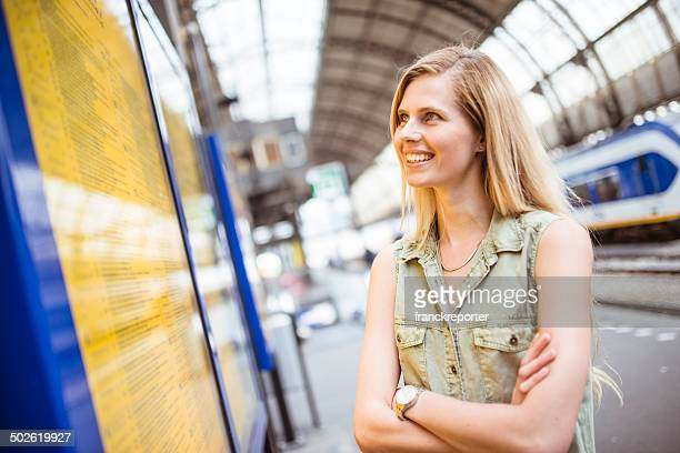 tourist in amsterdam looking the timetable at station