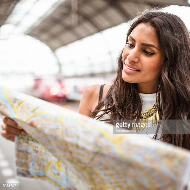 tourist in amsterdam station looking map of the city