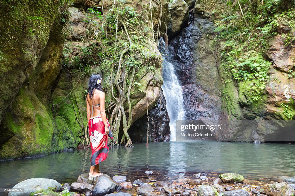 Tourist in front of waterfall in a tropical island, Fiji