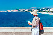 Adult woman reading a tourist brochure before visiting the city of Nice in the French Riviera region of France. AdobeRGB colorspace.