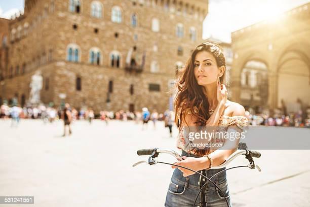 Tourist in piazza della signoria with a bike - florence