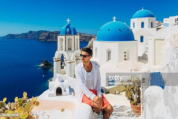 Tourist in sunglasses sitting in Oia village, Santorini island, Cyclades, Greece