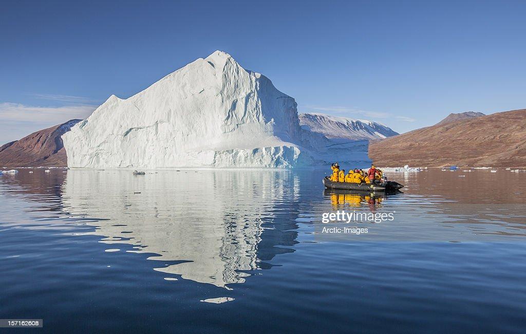 Tourist in Zodiac exploring icebergs, Scoresbysund : Stock Photo