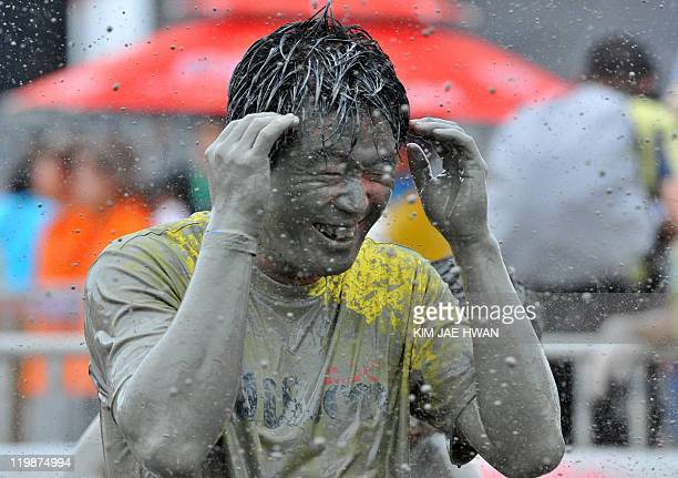 A tourist is covered with mud during the Boryeong Mud Festival at the Daecheon swimming beach in Boryeong 190 kilometers southwest of Seoul on July...