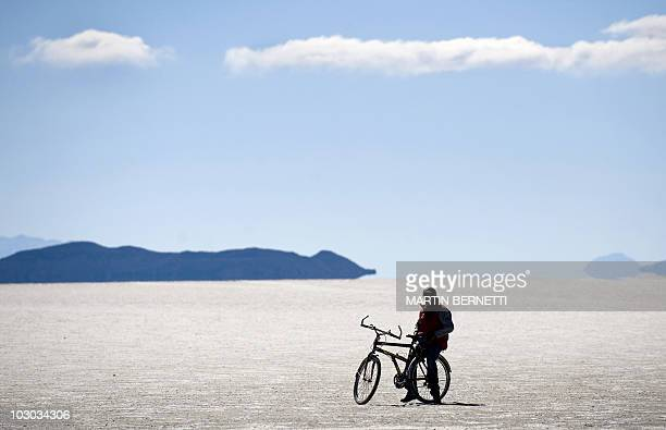 A tourist is seen on a bicycle in the Uyuni salt flats Bolivia on October 6 2009 The Uyuni salt flats are estimated to contain 10 billion tons of...
