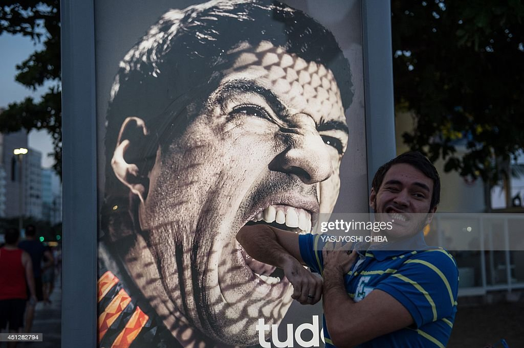 A tourist jokes in front of an advertisement with the portrait of Uruguay's forward Luis Suarez at Copacabana beach in Rio de Janeiro, Brazil, on June 26, 2014. Sportswear giant Adidas said Thursday it would stop using Luis Suarez, one of its key promotional stars, for World Cup adverts after his four-month ban from football activities for biting Italian Giorgio Chiellini.