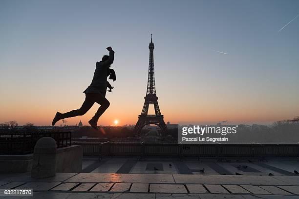 A tourist jumps in front of the Eiffel tower at sunrise on January 18 2017 in Paris France