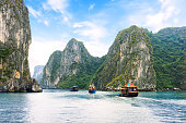 Tourist junks floating between limestone karsts and isles in Ha long Bay, Vietnam