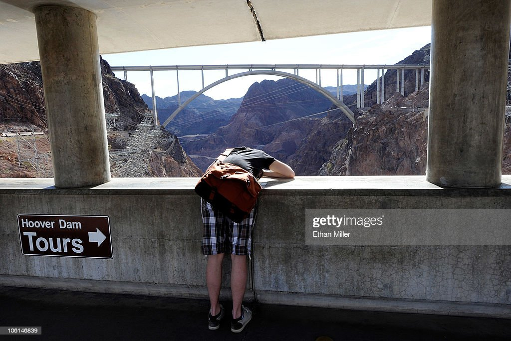 A tourist leans over a wall to take photos of the Hoover Dam with the Mike O'Callaghan-Pat Tillman Memorial Bridge part of the Hoover Dam Bypass Project visible in the background October 26, 2010 in the Lake Mead National Recreation Area, Nevada. The 1,900-foot-long structure sits 890 feet above the Colorado River, about a quarter of a mile downstream from the Hoover Dam. The USD 240 million four-lane bypass project to relieve vehicle traffic on the Hoover Dam began in 2003, and opened to traffic on October 19.