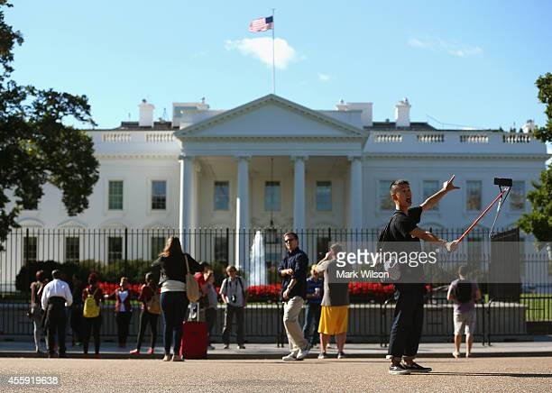 Tourist Li Cheng on vacation from Taiwan takes a selfie of himself standing in front of the White House September 22 2014 in Washington DC The US...